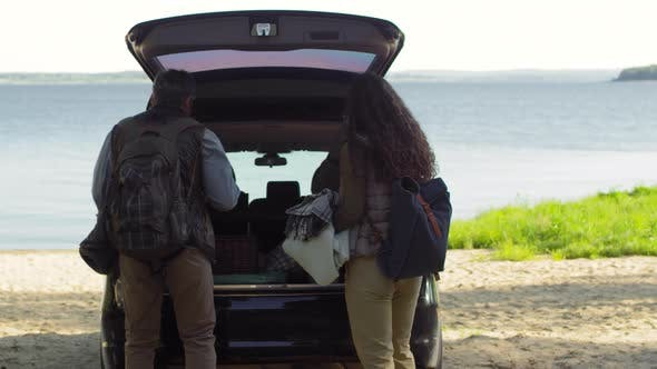 Thumbnail for Tourist Couple Putting Camping Supplies into Car Trunk before Ride