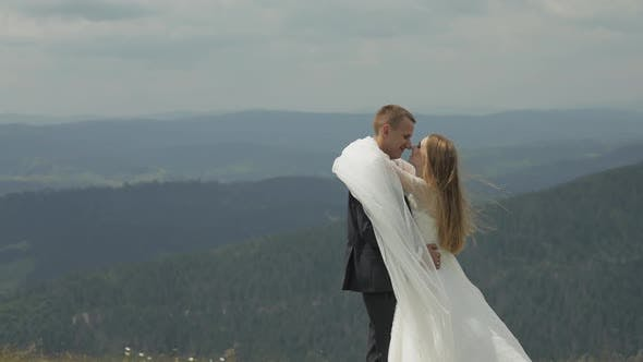 Thumbnail for Groom with Bride Having Fun on a Mountain Hills. Wedding Couple Hugging