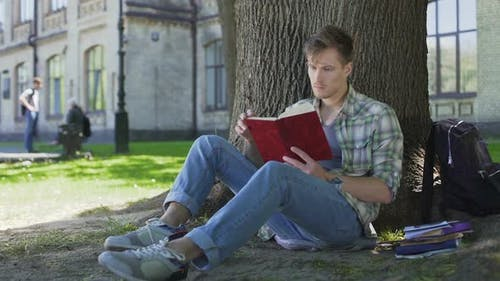 Male student skimming through pages of textbook, repeating learned material