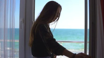 Woman with Long Hair Opening Balcony Doors and Looking Out at the Sea
