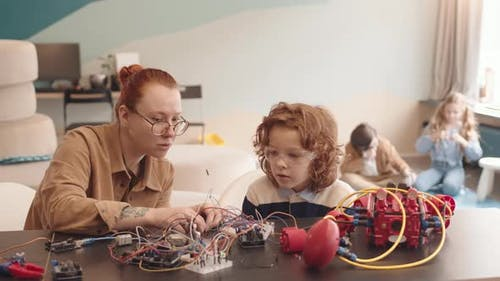 Young Teacher and Schoolboy Constructing Robot in Classroom