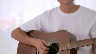 Happy Asian man playing guitar at the bedroom.
