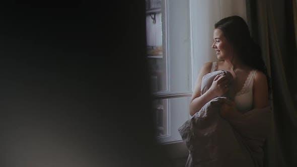 Thumbnail for Schöne glückliche Frau trifft warmen, sonnigen Morgen, stehend im Schlafzimmer durch Fenstertür und gewickelt