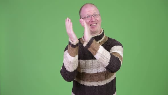 Thumbnail for Happy Mature Bald Man with Turtleneck Sweater Clapping Hands