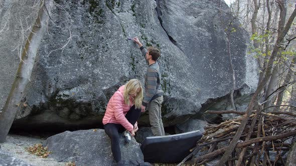 Thumbnail for Couple preparing to climb boulder as she puts on shoes
