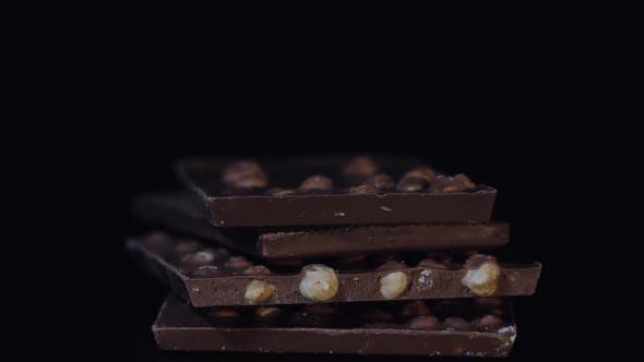 Dark Chocolate Blocks with Nuts Details Slow Close-up Macro. Chocolate Bars
