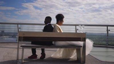 Wide Shot of Argued Newlyweds Sitting on Bench Back to Back