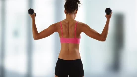 Thumbnail for Active black woman exercising with dumbbells.