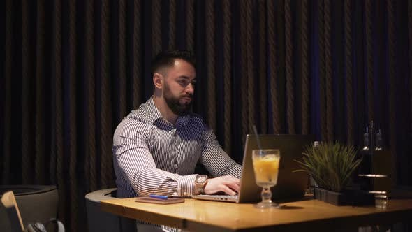 Bearded Businessman Working with Laptop on New Project, Sitting Alone on Cofe Table
