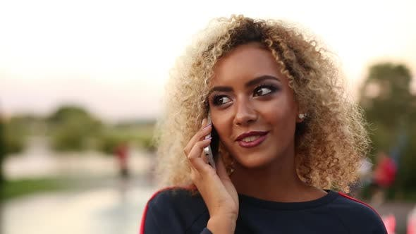 Thumbnail for Positivity Woman with Volumed Curly Hair Talking at Call Phone and Smiling
