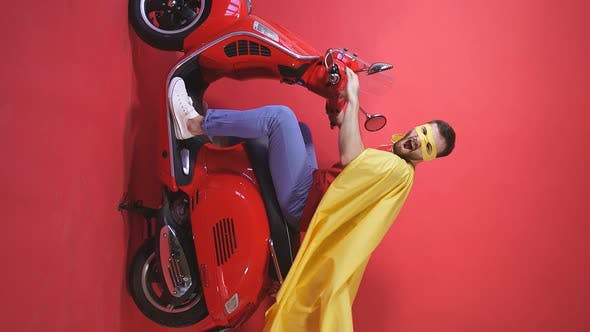 Portrait Young Man Riding Scooter To Theme Party Dressed Superhero Costume Isolated Background