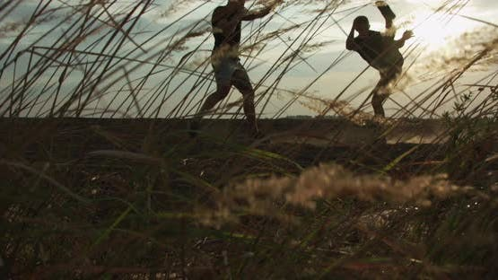 View Through the Blowing Wild Grasses Web of Two Fighters Performing Martial Art