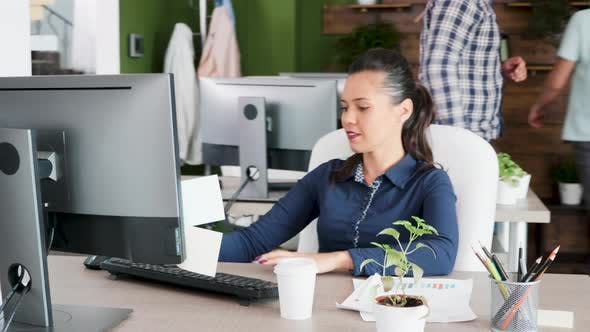 Cover Image for Beautiful Young Female Entrepreneur Typing and Enjoying Her Coffee at the Office