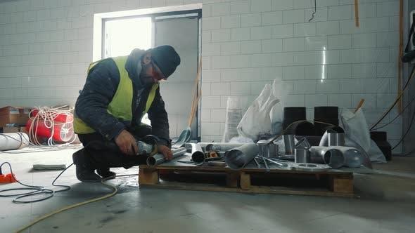 Ein Mitarbeiter schneidet eine Eisenpfeife mit einem bulgarischen Messer
