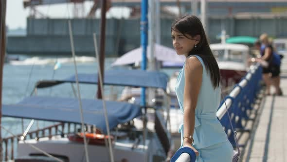 Thumbnail for Stylish Brunette Girl Standing in Dnipro Quay and Choosing a Yacht in Slo-mo
