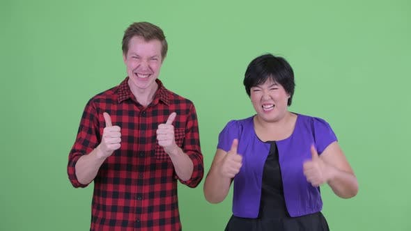 Thumbnail for Happy Young Multi Ethnic Couple Giving Thumbs Up Together