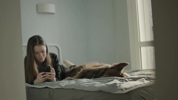 Young Woman At Home Using Her Smartphone Close To Her Dog.