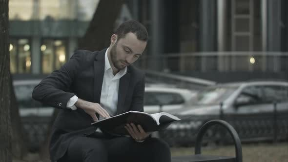 Man Is Sitting on a Bench in Park and Displeased Reading Business Plan