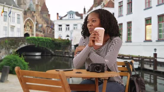 Thumbnail for Cute black female sits at table drinking cup of coffee on small street in Bruges