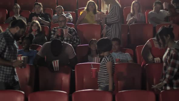 Diverse Audience Taking Seats in Cinema Hall