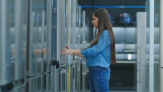 Cover Image for A Young Woman To Open the Refrigerator Door To Store Appliances and Compare with Other Models To Buy