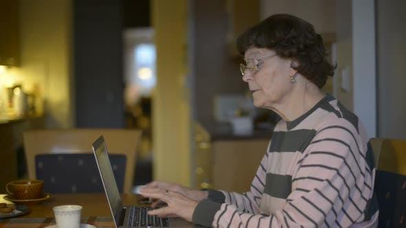 Happy Senior Woman Using Laptop at Home