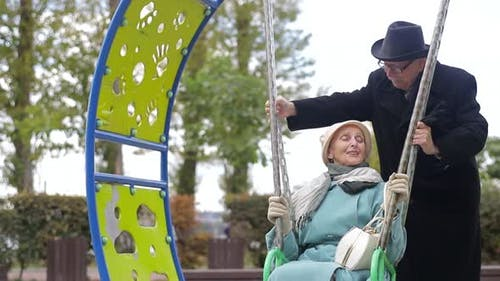 Seniorenpaar auf einem Spielplatz, schwingt auf der Schaukel.