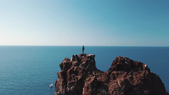 Thumbnail for Aerial View on High Rock and Statue on Its Peak. White Sailboat in Mediterranean Sea. Blue Sky