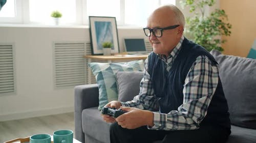 Slow Motion of Retired Man Enjoying Video Game in House Playing Alone Winning