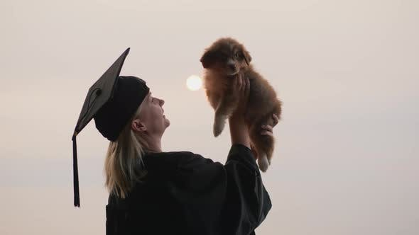Thumbnail for A Woman in a Graduate Costume Holds a Cute Puppy in Her Arm