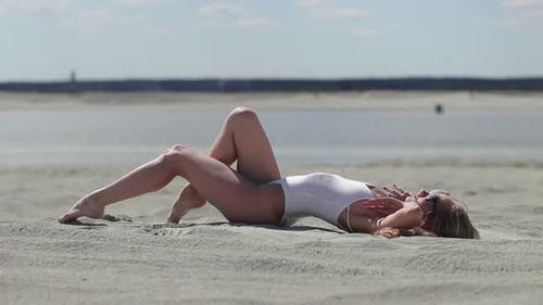 Charming Woman Sitting on Beach and Making Body Wave