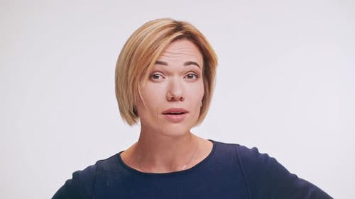 Caucasian Middleaged Female with Blonde Hair Standing on White Background Trying to Hear in