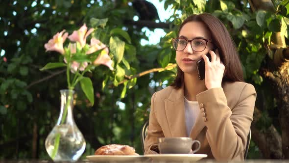 Young Business Woman Sits in a Cafe and Speaks on the Phone. Girl with Coffee and a Bun on the