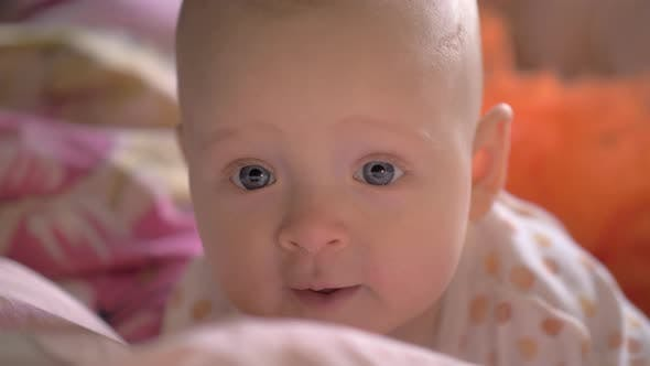 Portrait of Baby Girl with Big Blue Smiling Eyes