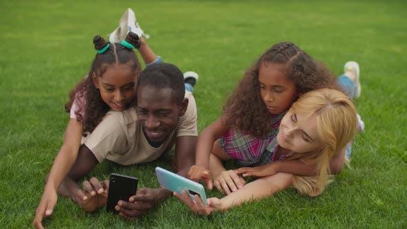 Thumbnail for Multiracial Family Taking Selfie Lying on Grass