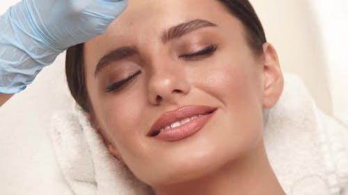 Woman at Beauty Clinic Receiving Facial Treatment