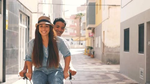 People, leisure and lifestyle concept happy young couple riding bicycle in the city - overjoyed