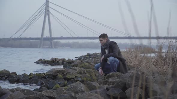 Thumbnail for Thoughtful Caucasian Young Man Sitting on Riverbank and Throwing Rocks in Water. Portrait of Sad