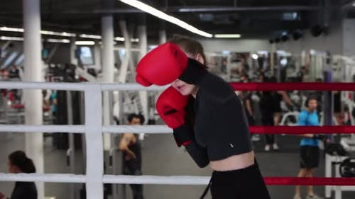 Young Woman Training Her Boxing on the Ring in the Gym