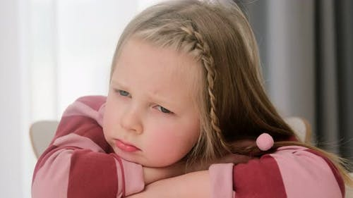 Sad upset offended child little girl sits at a desk. Kid punished, lonely problems