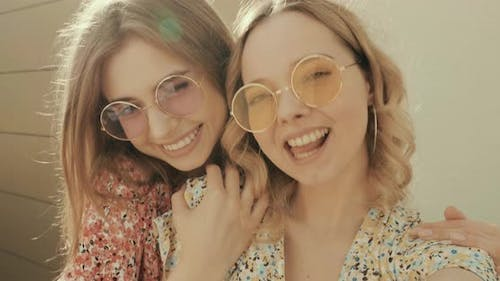 Portrait of two young beautiful smiling hipster girls in trendy summer sundress