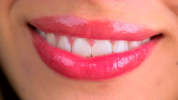 Thumbnail for Extreme close up of lips blowing a kiss and smiling