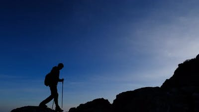 the Silhouette of a Man in the Mountains Against a Clear Sky