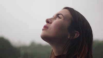 Young Sad Woman with Wet Hair Looks Up at Rain with Hope Cloudy Bad Weather