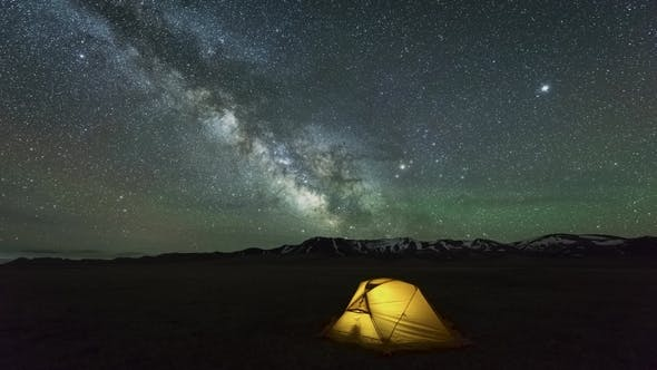 Thumbnail for Milky Way Is Moving Across Starry Sky with Airglow Over Yellow Glowing Tent