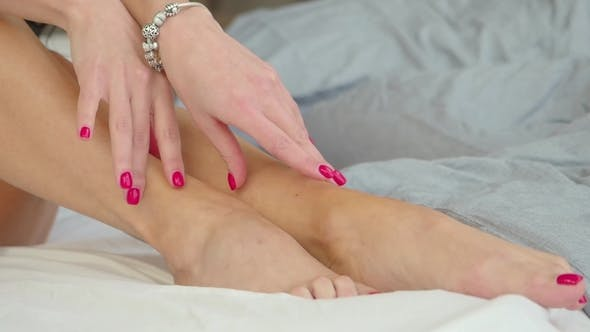 Thumbnail for Woman Touches Her Feet and Legs While Sits on the Bed Early in the Morning. Sensual and Sexy