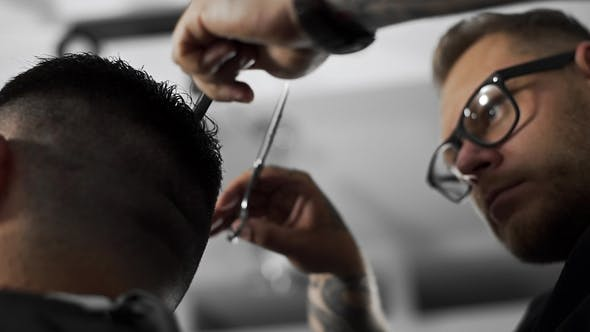 Thumbnail for Tattoed Barber Makes Haircut for Customer at the Barber Shop By Using Scissors and Comb