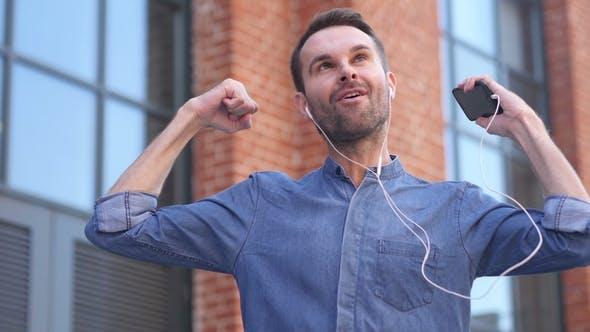 Happy Dancing Casual Man Listening Music on Smartphone
