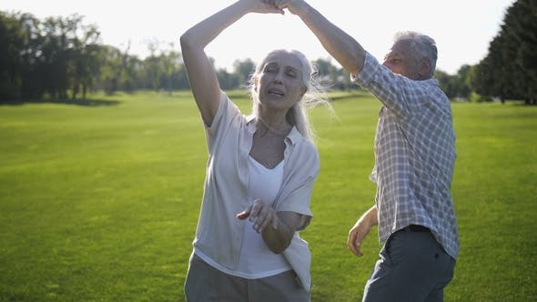 Thumbnail for Positive Mature Couple Dancing and Singing on Lawn