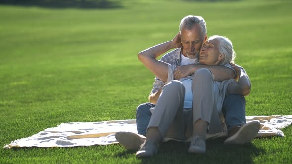Thumbnail for Affectionate Senior Couple Relaxing on Green Lawn